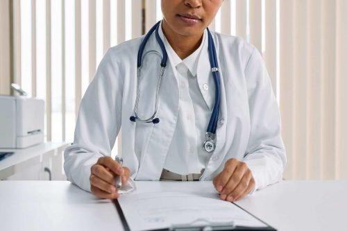 doctor writing in a clipboard